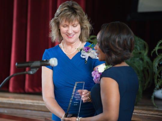 Karen Magnuson accepts an award from Jill Wynn during the Priceless Vessels: Women of Power Awards luncheon in 2015.