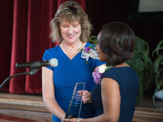 Karen Magnuson accepts an award from Jill Wynn during the Priceless Vessels: Women of Power Awards luncheon in 2015.
