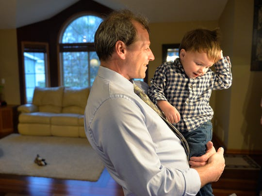 Chris Sutton smiles as he spends a little time with his youngest, Anthony, 2, after a day of work on Nov. 4. Sutton says his own research and advocacy helped him to survive three bouts with cancer and another with heart disease.