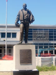 A statue of football legend Ernie Davis stands in front of its new home at Ernie Davis Academy in Elmira.