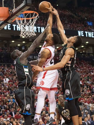 Toronto Raptors guard Norman Powell dunks between Milwaukee Bucks forward Giannis Antetokounmpo and Bucks forward Thon Maker during the fourth quarter in game five of the first round of the 2017 NBA Playoffs at Air Canada Centre.