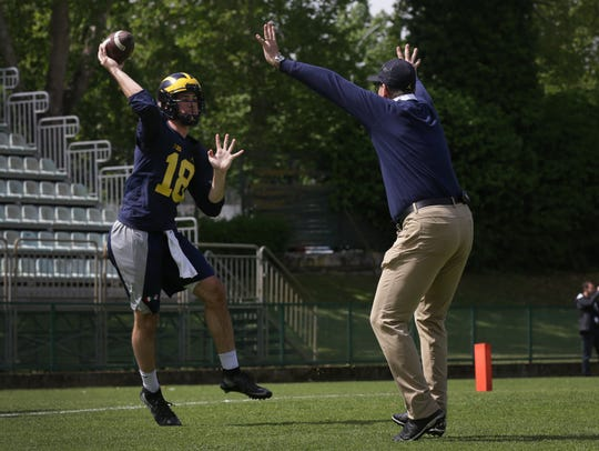 Michigan coach Jim Harbaugh practices a drill with
