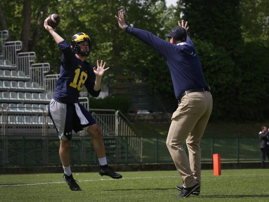 Michigan coach Jim Harbaugh practices a drill with Brandon Peters during the Wolverines first practice in Rome at Giulio Onesti Training Center on Thursday, April 27, 2017.