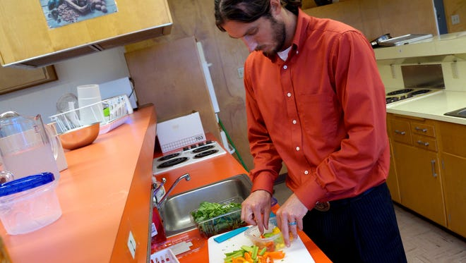 Jake Edmiston, a student in NMSU's Dietetic Internship Program, prepares an example of a healthy lunch for a child going back to school.