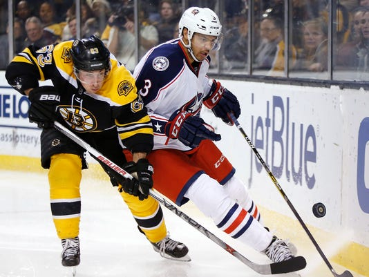 Boston Bruins' Brad Marchand (63) and Columbus Blue Jackets' Seth Jones (3) battle for the puck during the second period of an NHL hockey game in Boston, Monday, Feb. 22, 2016. (AP Photo/Michael Dwyer)