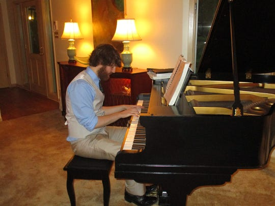 Sam Sphar plays the new baby grand piano at the Ruffins home.