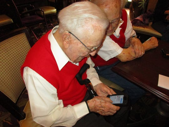 Albert Pfeufer shows his brother Elmer how he can text on an iPhone. Mar. 19, 2016.
