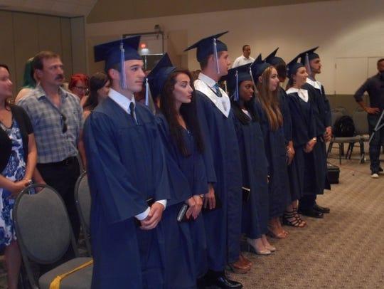 Graduates of Faith Christian Academy stand for the
