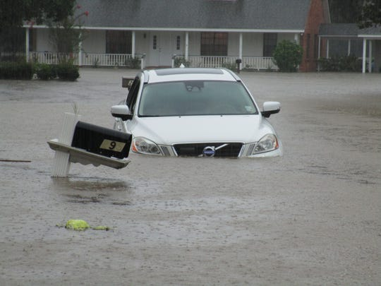 A car is submerged on a street near Comeax High School.
