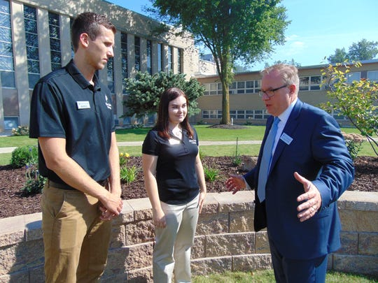 Dr. Chris E. Domes, president of Silver Lake College, far right, talks to students Luka Jovicic, left, and Ashley Rumlow during a celebration launching SLC Works, its Work College model.