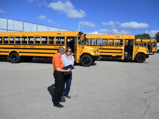 Mansfield City Schools Treasurer Robert Kuehnle and Transportation Supervisor Deb Rickert look over mileage and maintenance reports for the district's fleet of buses.
