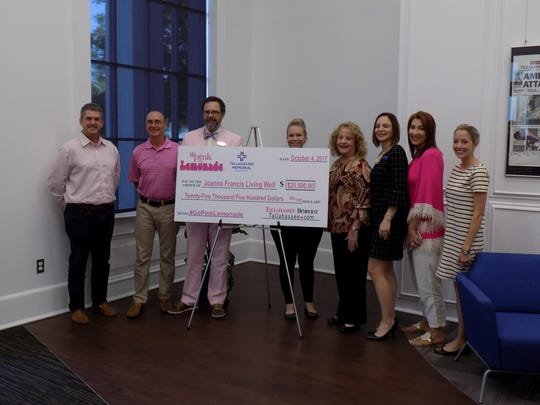 Representatives of the highest-earning businesses of the Go Pink lemonade stand fundraiser stand with a check of amassed funds in the Tallahassee Democrat lobby Wednesday.