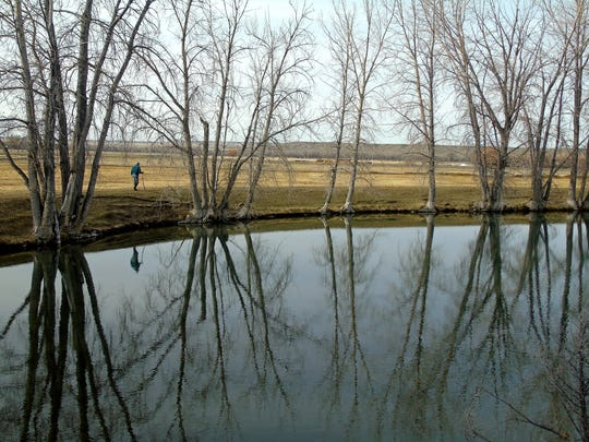 Ruth Mortag paces the pond on her ranch in the Sun