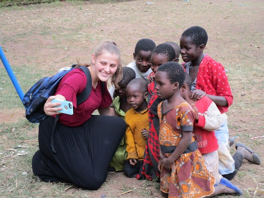 Danielle Snyder, 17, a senior at Olympic High School, takes a selfie with children in Njewa, Malawi. Snyder traveled there for humanitarian service this summer with her former second-grade teacher Kim Witte.