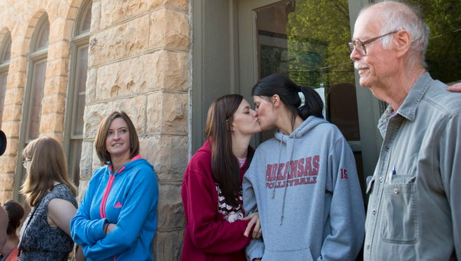 Jennifer Rambo, left, of Jacksonville, Ark., kisses her partner, Kristin Seaton, right, of Fort Smith, Ark., as they wait in line at the Carroll County Courthouse to apply for a marriage license.