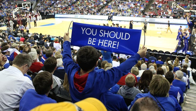 "A young fan holds up a ""You Should Be Here"" sign last March during the NCAA basketball tournament in Omaha. Des Moines will host March Madness games for the first time this week at Wells Fargo Arena. Local officials hope a good showing will lure the popular event back in future years."