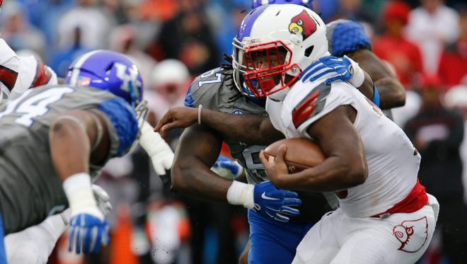 Louisville quarterback Lamar Jackson is wrapped up ater a long gain against UK in the second half. Nov,. 28, 2015.