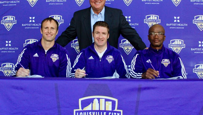 Louisville City FC coach James O'Connor, center, with assistants Daniel Byrd (left) and Thabane Sutu (right) and Louisville City chairman John Neace (back) as the trio sign their new contracts.