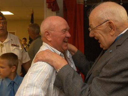 Hector Cafferata, Jr., right, shares a laugh with Ted Carpenter (CQ), an old friend, during the dedication ceremony for the elementary school named in honor of Cafferata in 2006..