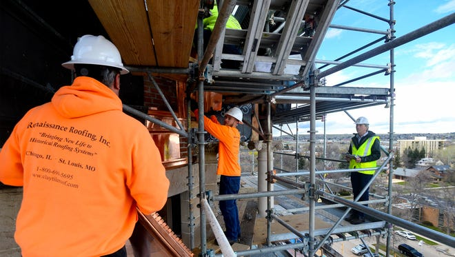 Renaissance Roofing Inc. project manager Lon Gorsch looks on as his crew fits new sheet copper on the dome of the Cascade County Courthouse.