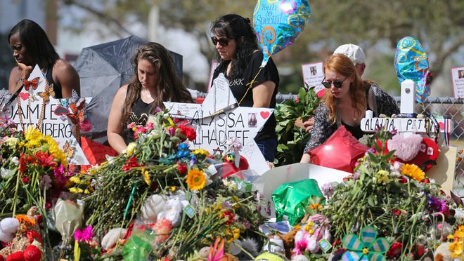 Mourners bring flowers as they pay tribute at a memorial for the victims of the shooting at Marjory Stoneman Douglas High School on Feb. 25 in Parkland, Fla.