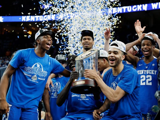 Kentucky players celebrate with their trophy after defeating Tennessee in an NCAA college basketball championship game at the Southeastern Conference tournament Sunday, March 11, 2018, in St. Louis. (AP Photo/Jeff Roberson)