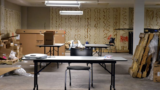 An empty desk sits among cardboard boxes and used office furniture in the basement of the Robert G. Clark building Friday in downtown Jackson.