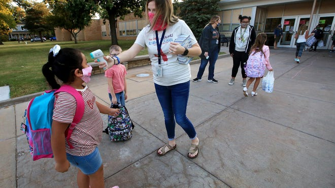 Teacher Lauryn Young takes the temperature of kindergartner Deborah Barrera as students arrive for the first day of school Thursday morning at McCandless Elementary School.