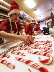 Gail Grumeley places completed candy canes on wax paper