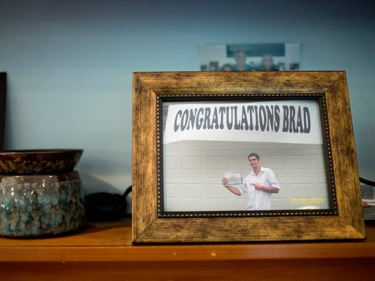 A framed photo from Bradley Moore's graduation party sits on a mantle in the family room.
