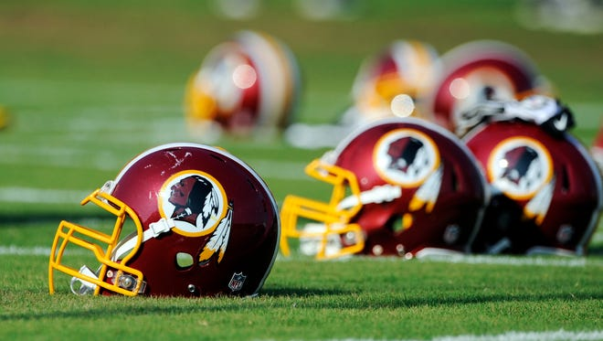 Washington Redskins helmets sit on the field during an NFL football minicamp in Ashburn, Va. The team mascot has drawn fire from critics and American Indian advocates who say the term 'Redskins' is a racial slur and should be changed by team owner Daniel Snyder. A report released Tuesday found that the use of Indian mascots contributes to low self-esteem for Native children.
