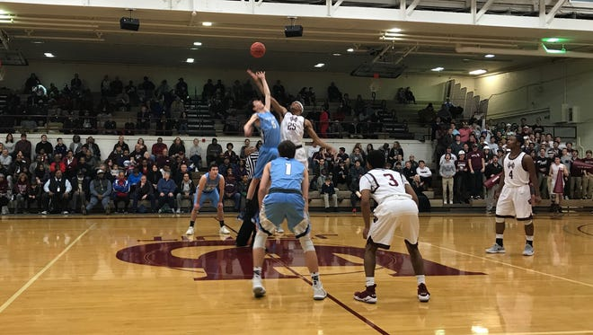 It's the opening tip Monday night between Livonia Stevenson's Thomas Demers (5) and University of Detroit Jesuit's Jalen Thomas (25). The host Cubs prevailed 72-49 in the Class A regional semifinal.