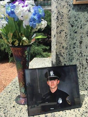 A photo of Officer Charles Irvine Jr. was placed at a memorial for fallen Milwaukee officers at MacArthur Square.