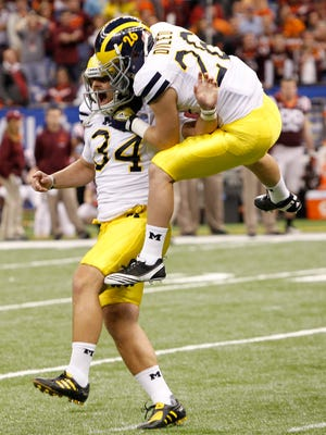 Michigan kicker Brendan Gibbons (34) celebrates with Drew Dileo (26) after his winning field goal in overtime against Virginia Tech in the Sugar Bowl NCAA college football game in New Orleans.