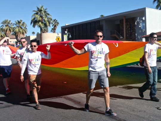 Marchers carry a rainbow flag Sunday during the Greater Palm Springs Pride parade in downtown Palm Springs. Thousands of people participated to show support for the LGBT community.