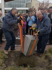 Two workers place the 50th anniversary time capsule