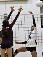 Alamogordo's Paige Harrell, right, tips a ball over the net.