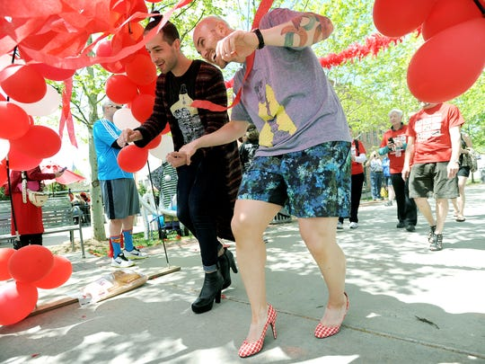 David Lytle, left, and James Sturgill hold on to one another for support as they reach the finish line of Walk a Mile Asheville at Pack Square Park on Saturday, May 2, 2015.  For a photo gallery from Saturday's event go to Citizen-Times.com