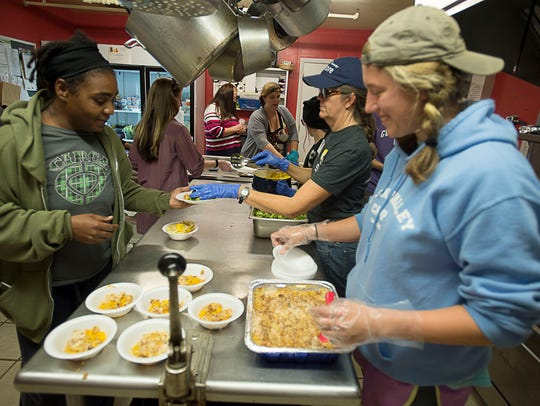 Volunteers serve a healthy, hot meal of tilapia, broccoli,