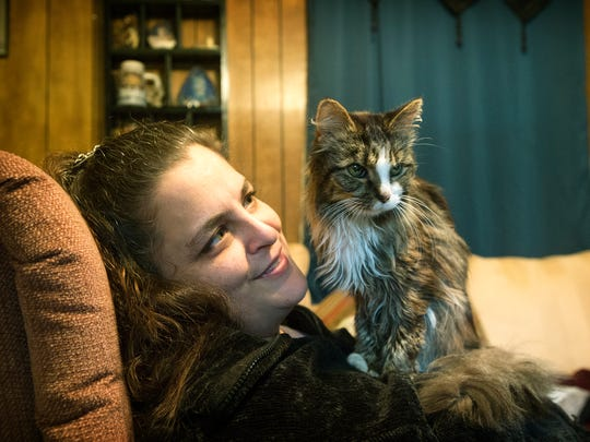 Kelly Thibeault plays with her cat, Baby Girl, as she sits in the home office she has set up in her living room to job search and fill out online applications at her home in Leicester on Monday. Thibeault said her two cats have helped her through the emotional hardships of being unemployed.