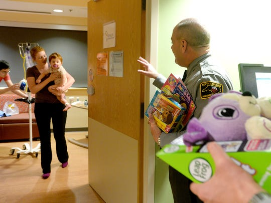 Kalane Jones carries her daughter, Arabella, 1, to the door to meet with First Sgt. Brian Gilreath and other members of the North Carolina Highway Patrol during their visit to Mission Hospital on Tuesday, Dec. 15, 2015.