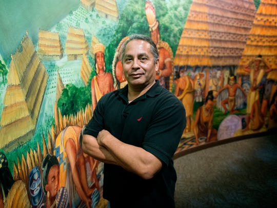 John Standingdeer poses in front of a mural inside