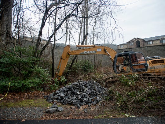 Harvey Huntley, with Huntley Construction, moves debris Wednesday at the site of a sinkhole on Cliffview Drive caused by the days of accumulating rain. The road leading to The Cliffs neighborhood has been closed until its safe again.