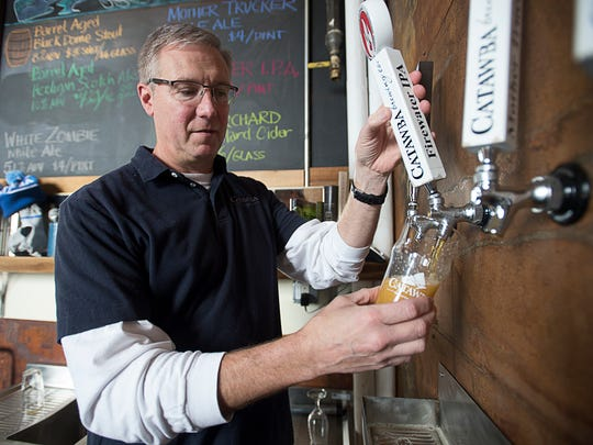 Catawba Brewing co-owner Billy Pyatt pours out a pint of Firewater IPA at their location on Banks Avenue.
