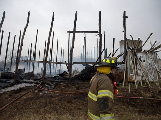 A firefighter walks by a destroyed barn after a fire off of Ivy Hill Road in Madison County on Saturday.