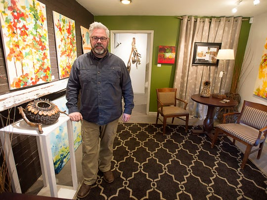 Sculptural basketry artist Matt Tommey stands next to one of his pieces on display inside his gallery and studio at the Riverview Station.