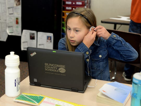 "Gracie Stevens, 10, puts headphones on to work independently in her fourth grade classroom at William W. Estes Elementary School on Thursday, Feb. 11, 2016. On of the values of ""The Leader in Me"" program the school has adopted teaches students to be accountable for themselves."