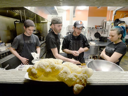 The Junction chef David Van Tassel, center right, prepares his staff, from left, Justin Shelton, Matt McKenna, and Teresa Bowser, for the night's dinner service on Friday, Feb. 19, 2016. On the service counter is a giant pork rind that which has become a signature for the restaurant.