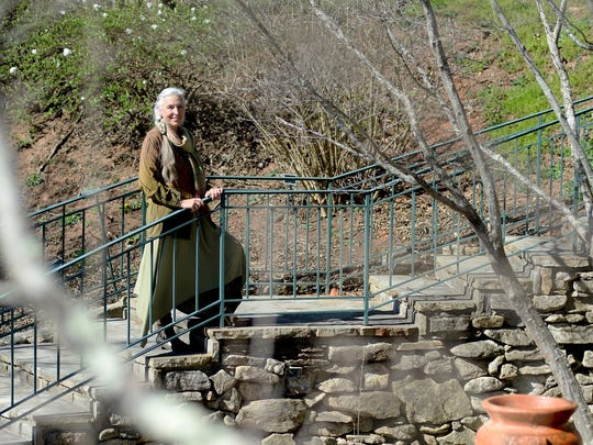 Shelli Stanback stands on a staircase surrounding a small waterfall on the grounds of the OM Sanctuary's meditation garden on Wednesday, March 23, 2016. The non-profit has placed much of their 54 acre property on a conservation easement protecting an urban forest near the French Broad River.