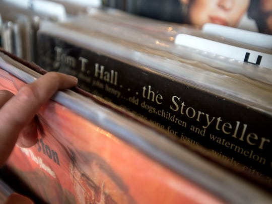 A patron looks through a stack of vinyl records (photo illustration).
